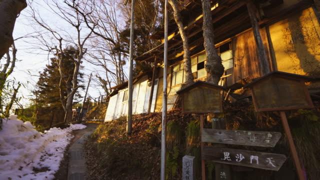 sunset light illuminates the ruins along the footpath at edge of town at shibu onsen (shibu hot spring) yudanaka, nagano japan on feb. 18 2019. - joshinetsu kogen national park stock videos and b-roll footage