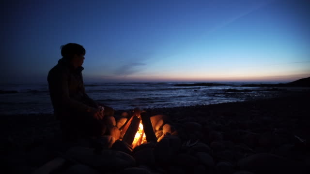 Sunset, man sits by campfire on beach