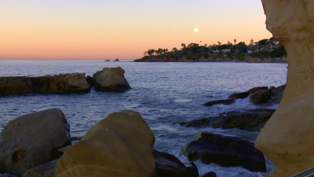 wide angle of cove in laguna beach at sunset. moon visile in sky. - カリフォルニア州 ラグナビーチ点の映像素材/bロール