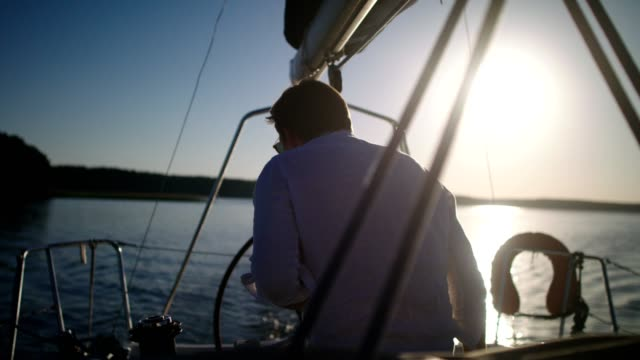 sunset on a lake. young man enjoying sailing - sailing stock videos & royalty-free footage