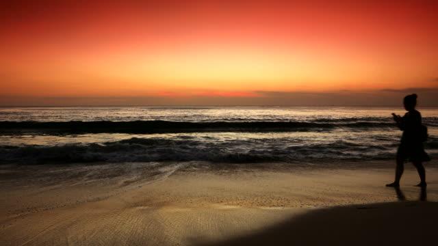 スマート フォンを使用して歩いている女性と熱帯のビーチに沈む夕日