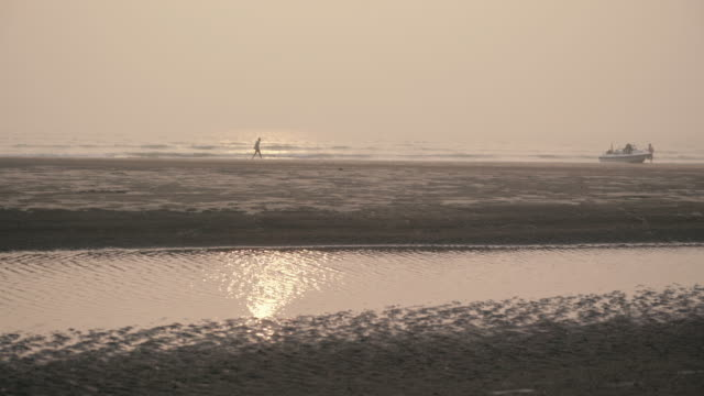 sunset on the beach as people get into a boat in the distance - cox's bazaar stock videos and b-roll footage