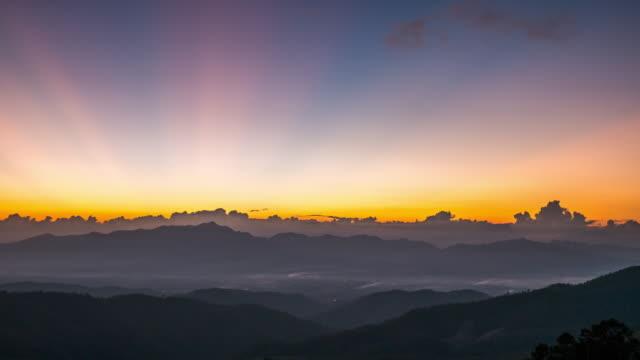 vídeos de stock, filmes e b-roll de pôr do sol na montanha com dia nublado de movimento a hora do crepúsculo - horizonte