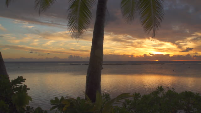 sunset over a lagoon in the tropical islands in french polynesia. - french polynesia stock videos & royalty-free footage