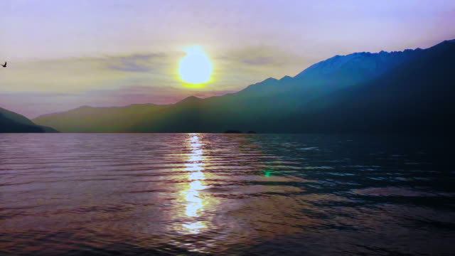 vídeos de stock e filmes b-roll de sunset over alpine lake with mountain and a bird flying - ilha