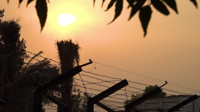 sunset over barb wire at the india pakistan border - military exercise stock videos & royalty-free footage