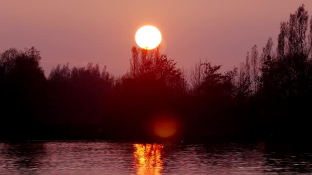 vídeos de stock, filmes e b-roll de pôr do sol sobre o big river intervalo de tempo - céu romântico