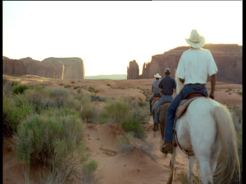 sunset over buttes, horsemen ride past camera, monument valley - recreational pursuit stock videos & royalty-free footage