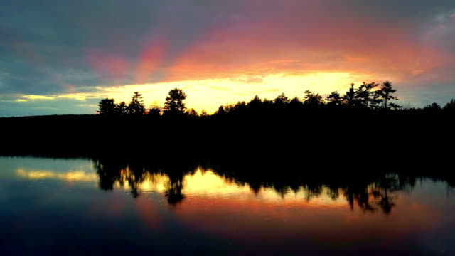 vidéos et rushes de sunset over calm upper peninsula michigan lake - michigan