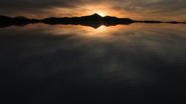 ws sunset over flooded salar de uyuni and andean peaks / daniel campos, potosi, bolivia - ウユニ塩湖点の映像素材/bロール