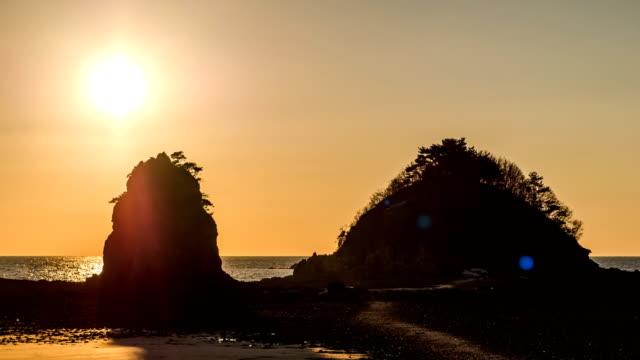 sunset over kkotji beach with halmibawi and harabibawi rocks / anmyeondo island, chungcheongnam-do, south korea - 松の木点の映像素材/bロール