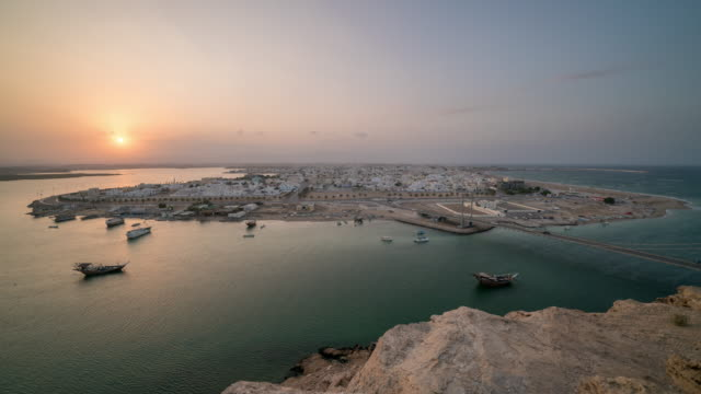 vídeos y material grabado en eventos de stock de puesta de sol sobre la ciudad portuaria de mar del medio oriente - omán