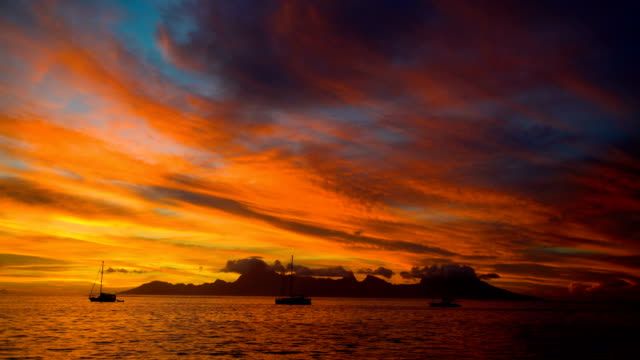 sunset over moorea island from tahiti south pacific - moorea stock videos and b-roll footage