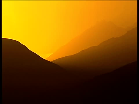 stockvideo's en b-roll-footage met sunset over mountains silhouetted against orange sky afghanistan - afghanistan
