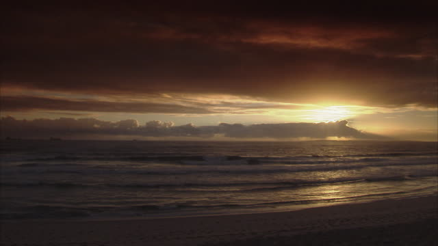 ws pan sunset over ocean and table mountain covered with clouds / cape town, south africa - ケープ半島点の映像素材/bロール