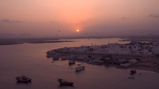 vídeos y material grabado en eventos de stock de puesta de sol sobre el puerto, los pájaros vuelan en el cielo - omán