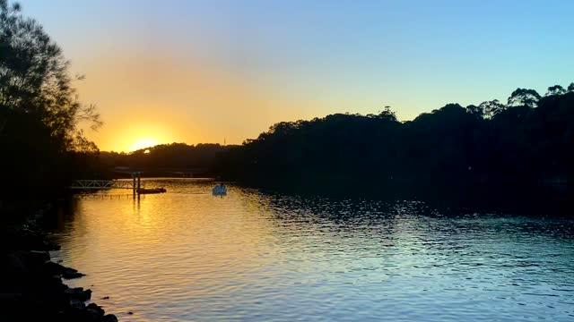 sunset over river boat with coastline trees - water's edge bildbanksvideor och videomaterial från bakom kulisserna