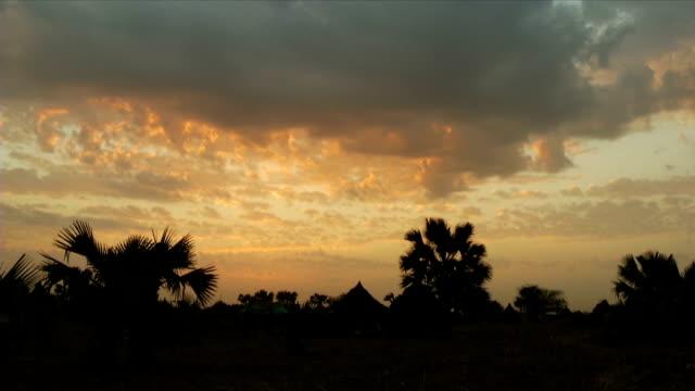 vídeos de stock, filmes e b-roll de ws sunset over rural village and huts / gogrial/ south sudan - sudão