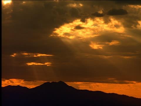 vídeos de stock, filmes e b-roll de sunset over silhouette of mountains - céu romântico