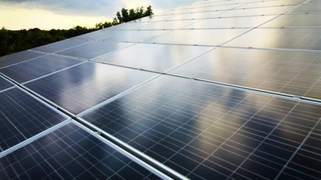 vidéos et rushes de coucher du soleil au-dessus du panneau solaire array - neuf