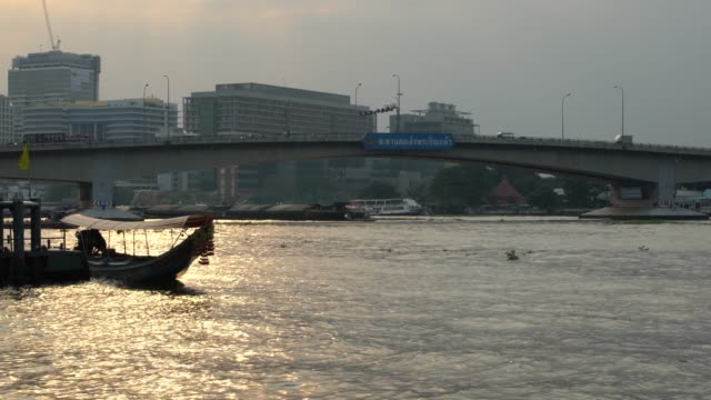 sunset over the famous chao phraya river in the central parts of bangkok, thailand - ウォータースポーツ点の映像素材/bロール