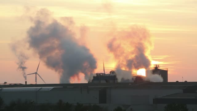 Sunset over the Iggesund paper board manufacturer in Workington, Cumbria, UK, at sunset, with wind turbines. The plant is powered by a biofuel power station, on site.