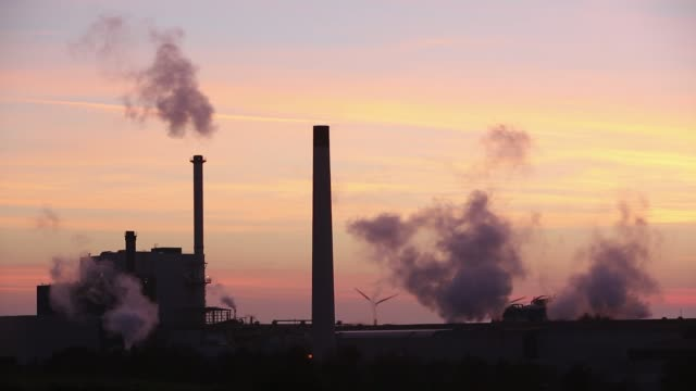 sunset over the iggesund paper board manufacturer in workington, cumbria, uk, at sunset, with wind turbines. the plant is powered by a biofuel power station, on site. - smoke stack stock videos and b-roll footage
