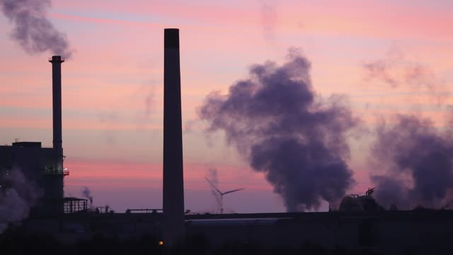 sunset over the iggesund paper board manufacturer in workington, cumbria, uk, at sunset, with wind turbines. the plant is powered by a biofuel power station, on site. - dämmerung stock-videos und b-roll-filmmaterial
