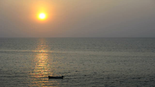 Sunset over the ocean and a small anchored motorboat/Luanda/ Angola