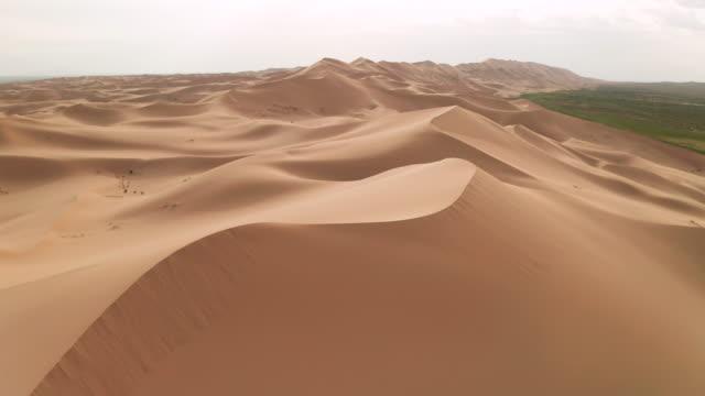 vidéos et rushes de sunset over the sand dunes in the desert. aerial view - paysage aride