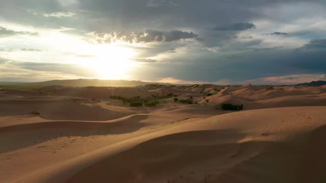 vidéos et rushes de sunset over the sand dunes in the desert. aerial view - désert de gobi