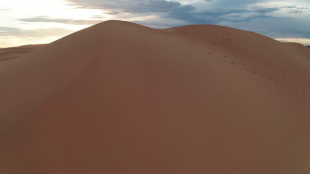 vídeos de stock e filmes b-roll de sunset over the sand dunes in the desert. aerial view - duna