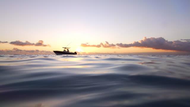 Zonsondergang boven de zee, terwijl een boot langzaam voorbij