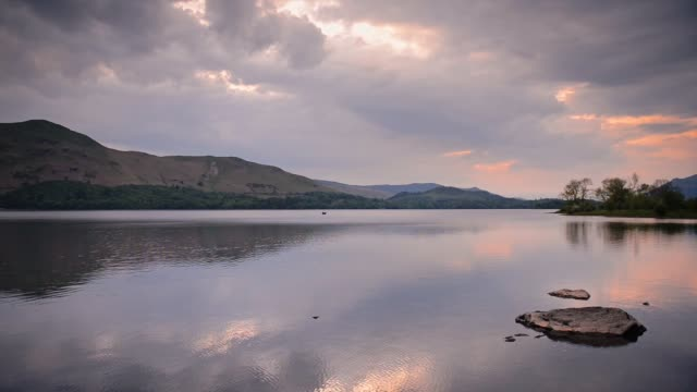 sunset over the serene lake with reflections of clouds and mountains on the water surface in lake district, cumbria, england.- wide shot - water stock videos & royalty-free footage