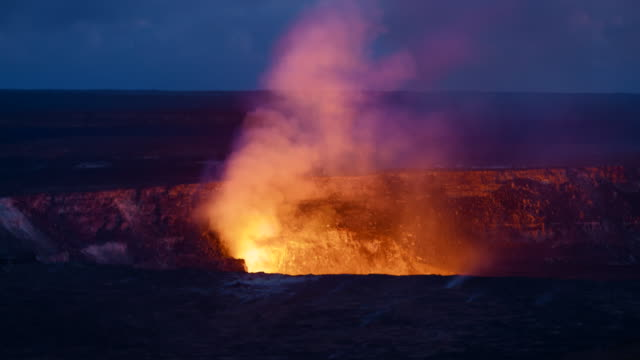 Sunset over volcano in Hawaii brings out the glow of the molten lava in the crater