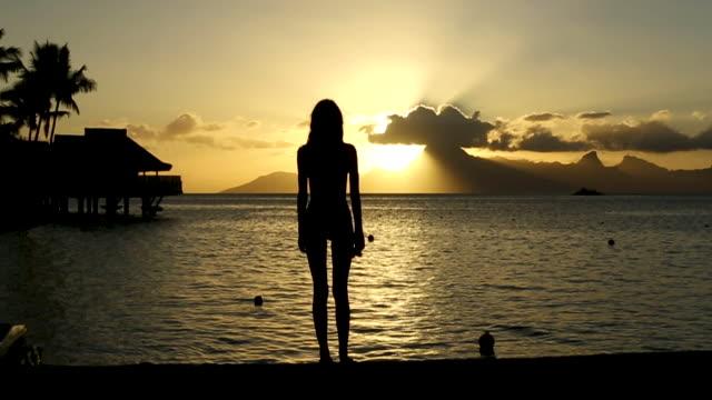 sunset over woman on tahiti beach, wide - tahiti stock videos & royalty-free footage