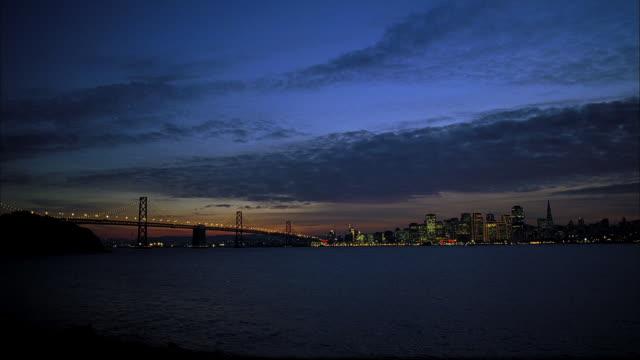 sunset paints the sky above san francisco's golden gate bridge. - san francisco bay stock videos & royalty-free footage