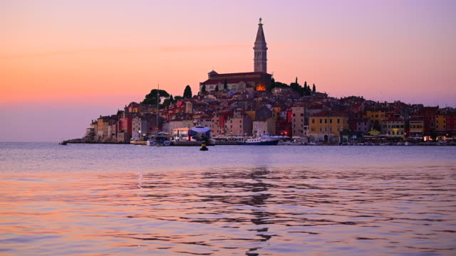 sunset scene of rovinj old town and basilica of st. euphemia, rovinj, istria, croatia - mare adriatico video stock e b–roll