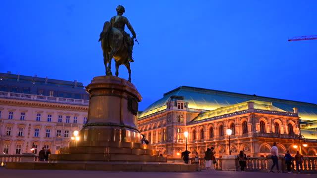 オーストリア・ウィーン、ウィーンのウィーン・オペラハウス前を歩く交通道路と人々の夕焼けシーン - カールスプラッツ点の映像素材/bロール