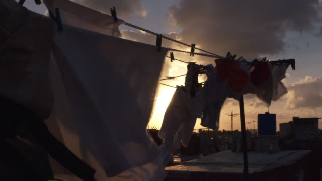 stockvideo's en b-roll-footage met sunset scenery between laundry hanging on clotheslines / havana, cuba - wasknijper