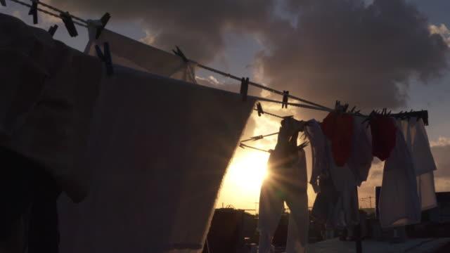 stockvideo's en b-roll-footage met sunset scenery between laundry hanging on clotheslines / havana, cuba - wasknijper