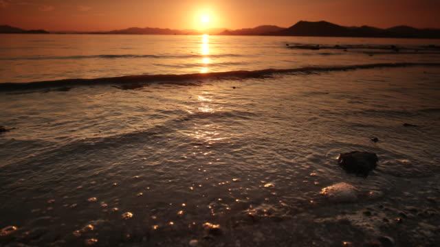 sunset scenery over surfs on the beach / sinan-gun, jeollanam-do, south korea - south pacific ocean点の映像素材/bロール