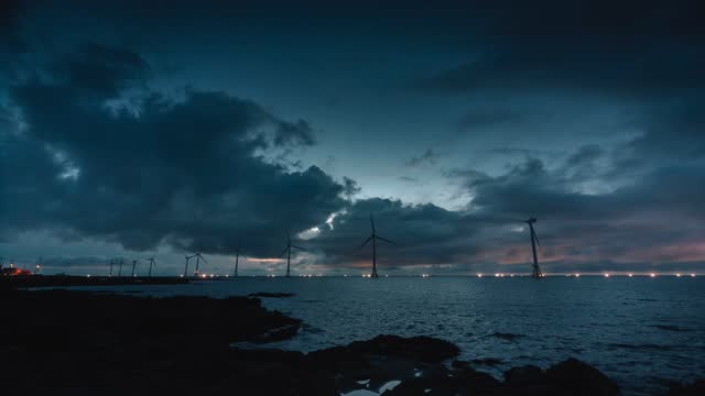 sunset scenery with wind turbine / jeju-do, south korea - 照明器具点の映像素材/bロール