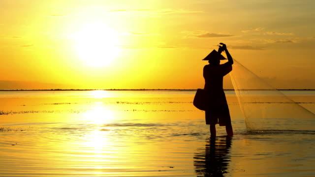 sunset silhouette balinese fisherman casting a fishing net - fisherman stock videos & royalty-free footage