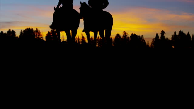 Sunset silhouette reveal Cowboy Riders in wilderness USA