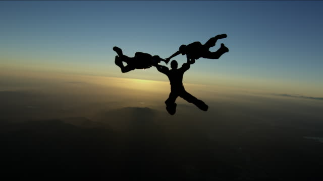 sunset silhouette skydiving - three people stock videos & royalty-free footage
