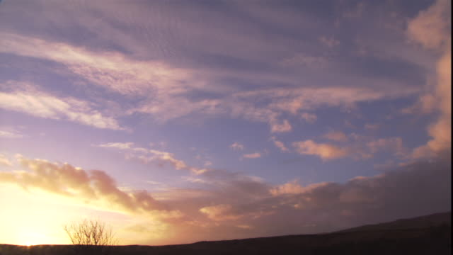 a sunset silhouettes rolling hills against wispy clouds. - cumulus stock videos & royalty-free footage