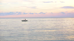 sunset Small boat sailing at sea