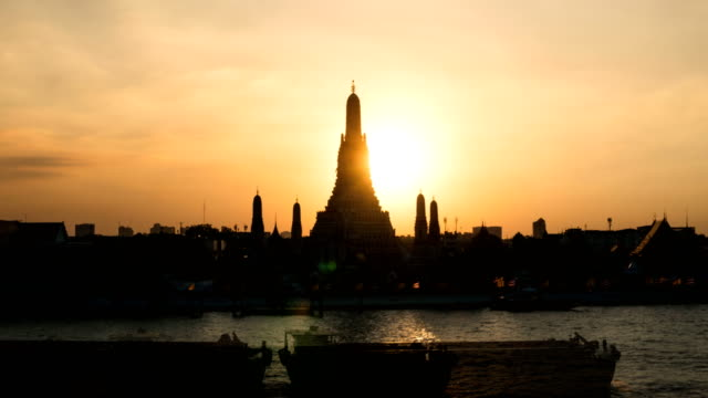 Sunset The iconic Temple of Dawn Time-lapse day to night, Wat Arun, along the Chao Phraya river with a colorful sky in Bangkok, Thailand