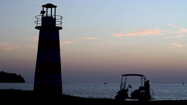 sunset time and a lighthouse in the golf course - pier stock videos & royalty-free footage